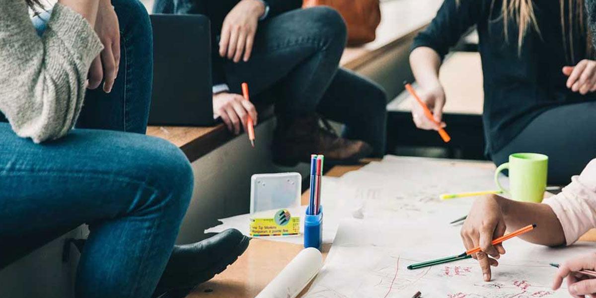 Menschen sitzen, skizzieren und diskutieren