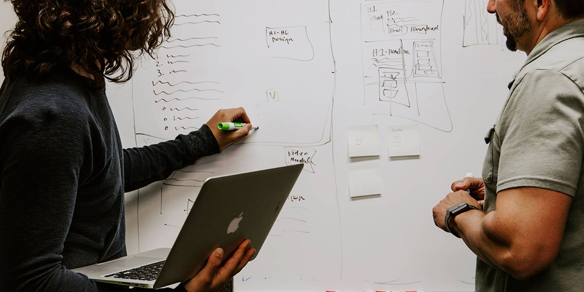 2 Menschen stehen und zeichnen auf einem Whiteboard