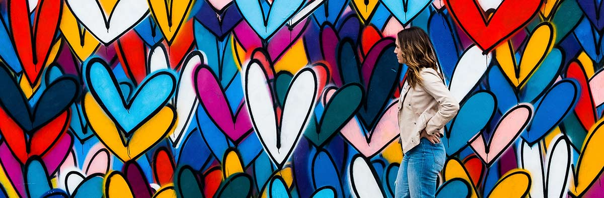 Frau steht vor mit Herzen gesprühter Wand