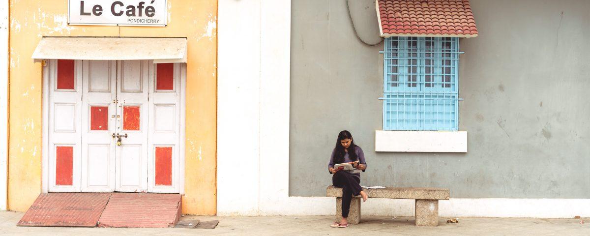 Frau sitzt auf einer Bank vor einem Gebäude vertieft in eine Arbeit